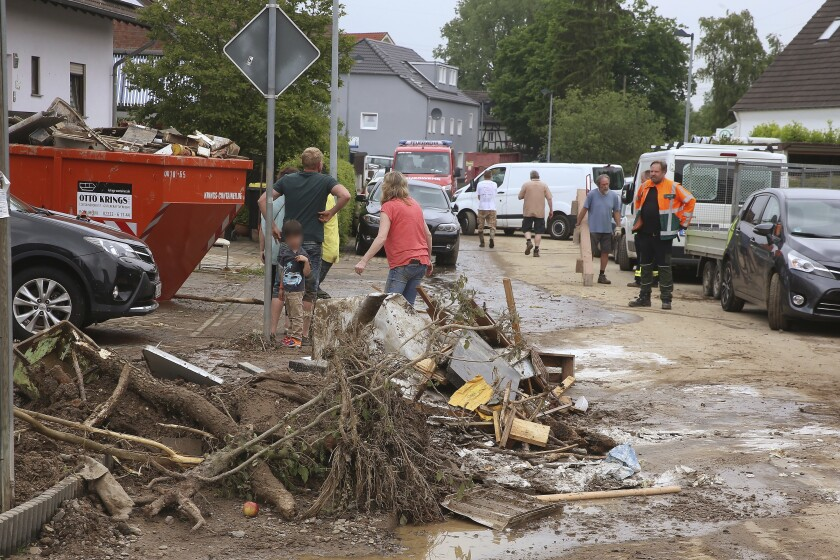 Residents and firefighters stand in a street covered in mud and debris in the Lanzenbach district, after an overnight storm in Hennef, Germany, Saturday, June 5, 2021. German authorities have issued severe weather warnings for parts of western Germany, a day after a man was killed and a 12-year-old girl was seriously injured in separate storm-related incidents. (David Young/dpa via AP)