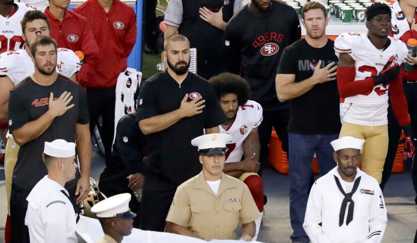 Former Green Beret Nate Boyer, second from right, stands next to a kneeling Colin Kaepernick during the national anthem on Thursday.