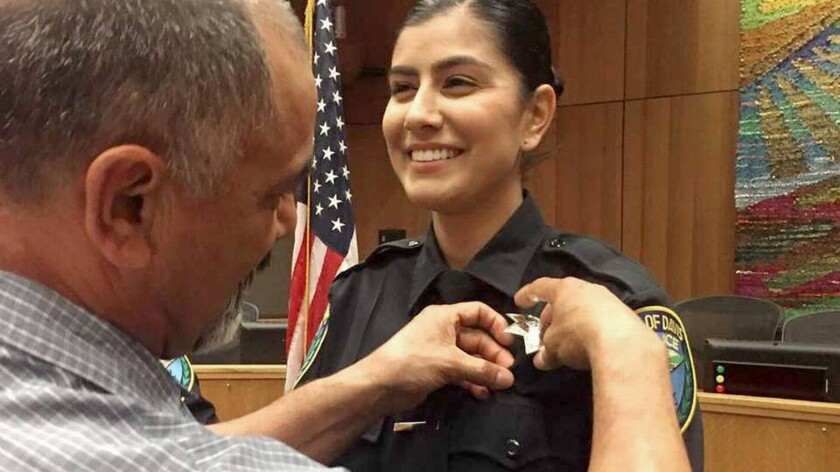 Merced Corona, left, pins his daughter Natalie Corona's badge on her uniform during a swearing-in