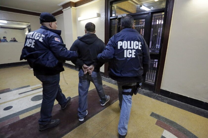 FILE- In this March 3, 2015 photo, Immigration and Customs Enforcement officers escort an arrestee in an apartment building, in the Bronx borough of New York, during a series of early-morning raids.