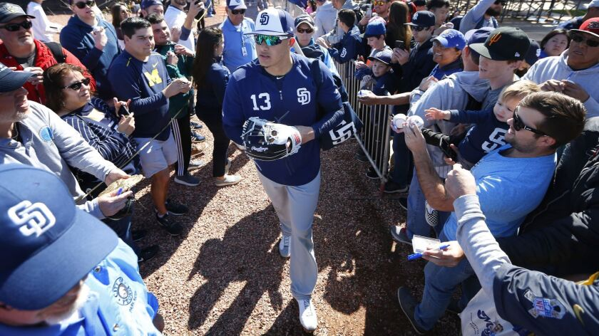 Padres' newly-signed third baseman Manny Machado signs autographs after a spring training workout on Feb. 23 in Peoria, Ariz.