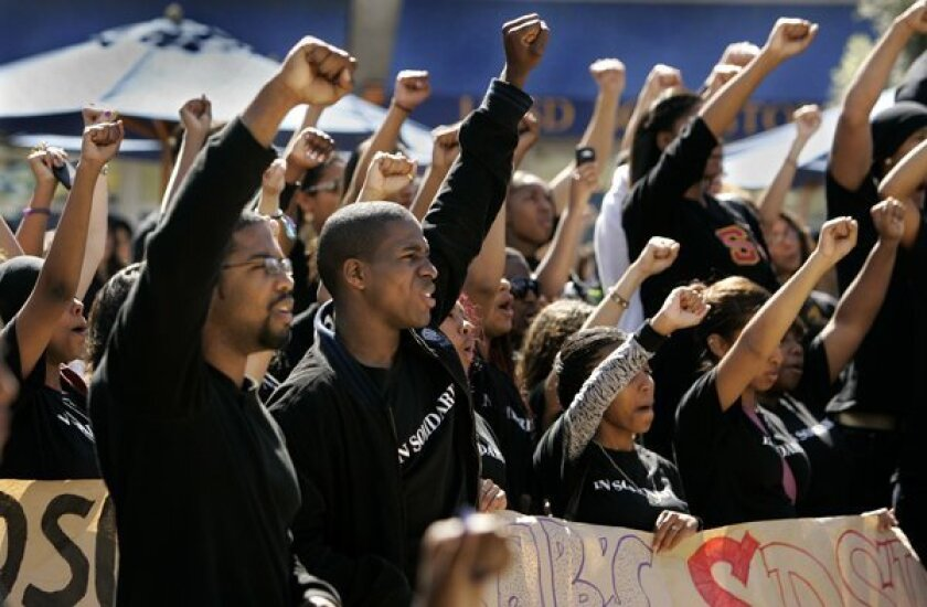 UC San Diego students and  supporters raise fists in solidarity during a Black Student Union press conference turned rally.