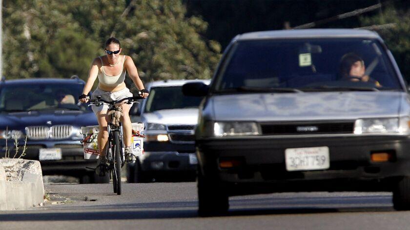 A bicyclist makes her way through traffic near the Glendale/Burbank/Griffith Park border Thursday Ju