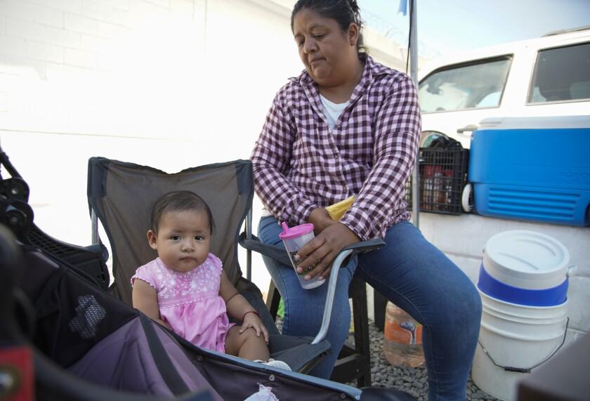 Karina Amaya 42, cuida a un bebé mientras vende refrescos en Tijuana
