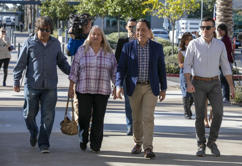 Todd Gloria, center, candidate for mayor, with his parents Linda and Phil Gloria , left, and his partner Adam Smith walked into the County Registrar of Voters office to vote on election day, Tuesday March 3, 2020.