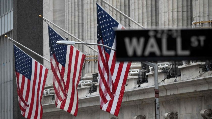 U.S. flags are flown outside the New York Stock Exchange on a rainy May 23.