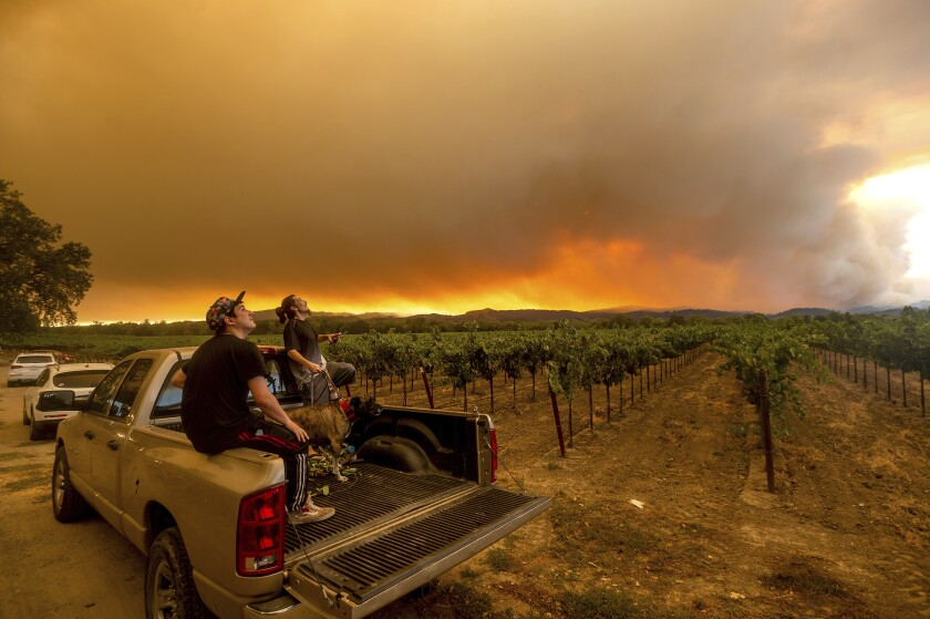 Thomas Henney and Charles Chavira watch a plume spread over Healdsburg, Calif., as the LNU Lightning Complex fires burn