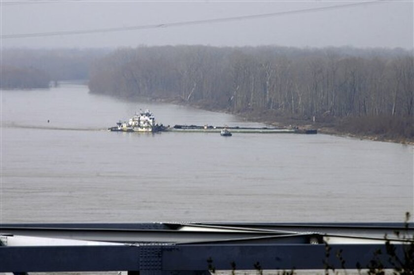 The towboat Nature Way Endeavor banks a barge against the western bank of the Mississippi River Sunday, Jan. 27, 2013 near Vicksburg, Miss.  A barge carrying thousands of gallons of oil struck a railroad bridge and began leaking before dawn Sunday. The accident forced the closure of a 16-mile stret