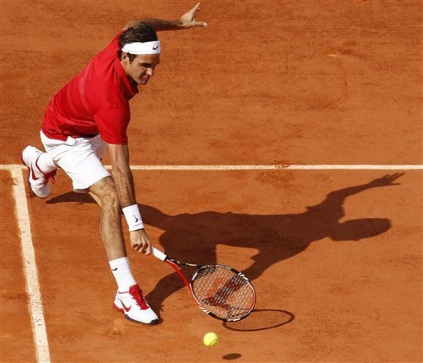 Roger Federer of Switzerland returns against Gael Monfils of France in the quarter final match of the French Open tennis tournament in Roland Garros stadium in Paris, Tuesday May 31, 2011. (AP Photo/Lionel Cironneau)