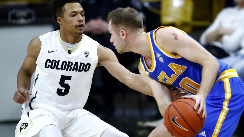 UCLA guard Bryce Alford protects the basketball as Colorado guard Deleon Brown takes a swipe at it during the second half Thursday.