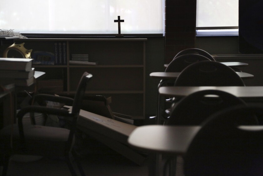 In this June photo, a cross sits in the window of an empty classroom at Quigley Catholic High School in Baden, Pa.