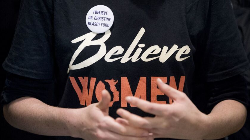 """A woman wears a shirt that reads """"Believe Women"""" with a button that reads """"I Believe Dr. Christine Blasey Ford."""""""