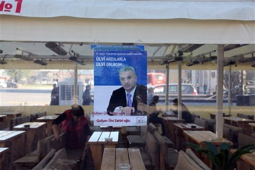 Electoral poster of a parliamentary candidate, Quliyev Ulvi, is displayed on a tea house in central Baku, Azerbaijan, Thursday, Nov. 4, 2010. Parliamentary elections in Azerbaijan are due on Sunday. (AP Photo/Manoocher Deghati)