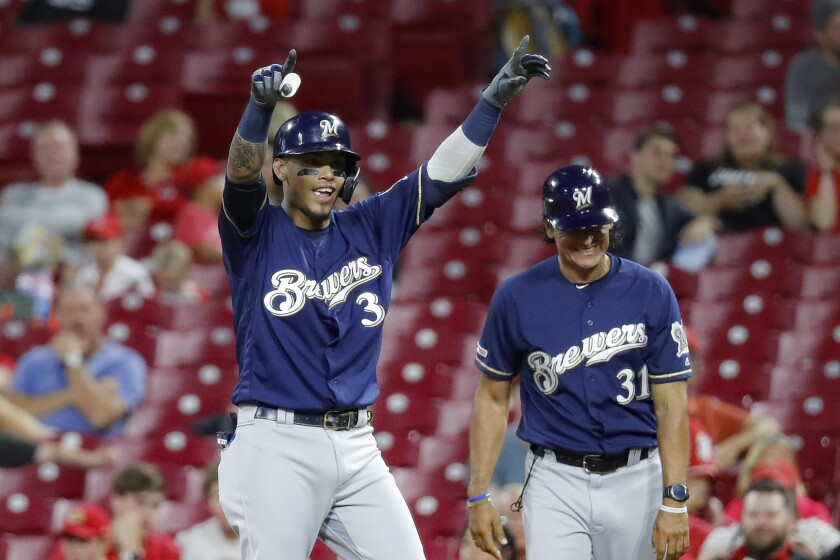 Milwaukee Brewers' Orlando Arcia reacts after reaching on a bunt single off Cincinnati Reds relief pitcher Kevin Gausman during the ninth inning of a baseball game, Tuesday, Sept. 24, 2019, in Cincinnati. (AP Photo/John Minchillo)