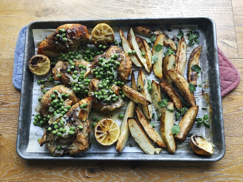 This image taken Sept. 6, 2020 in Alexandria, Va., shows a recipe for roasted chicken, potato wedges and green peas prepared in a sheet pan. This easy-to-prep, easy-to-cook, easy-to-clean, all-in-one-pan method can be applied to lots of different dinners. (Elizabeth Karmel via AP)