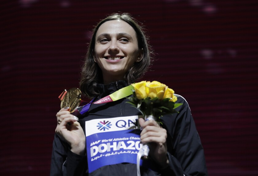 Mariya Lasitskene, who participates as a neutral athlete, poses during the medal ceremony for the women's high jump at the World Athletics Championships in Doha, Qatar on Oct. 1, 2019. Three-time world high jump champion Mariya Lasitskene has assailed Russian track leaders after they were charged with using fake medical documents during an investigation. Lasitskene has called for swift and radical reforms and the removal of officials appointed by track federation president Dmitry Shlyakhtin.
