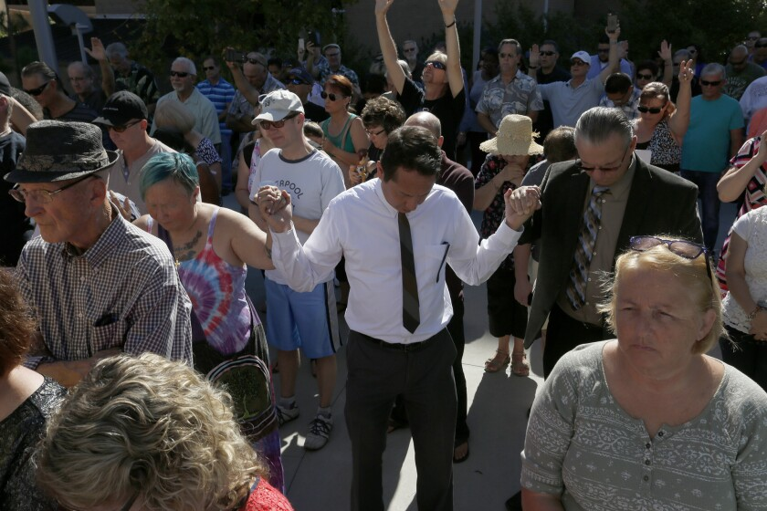 Members of the community pray outside the El Cajon Police Department.