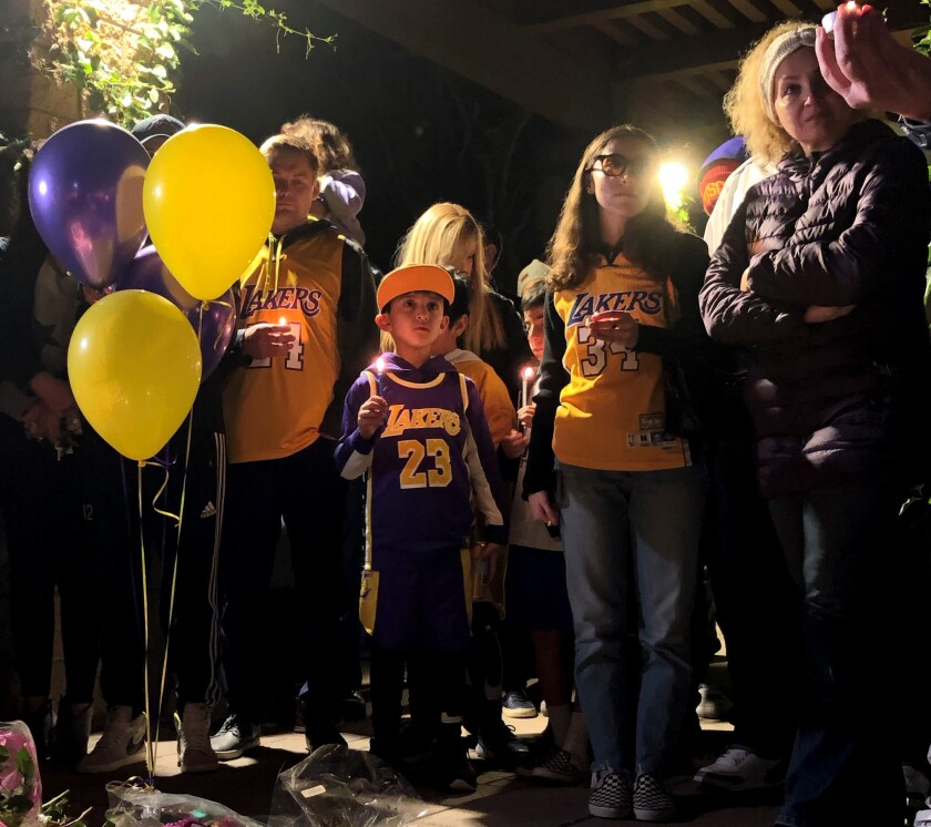 Newport Beach residents gather Sunday at a vigil mourning the loss of those killed in the Sunday helicopter crash, including seven who were from Newport Beach, Kobe Bryant and his daughter among them.