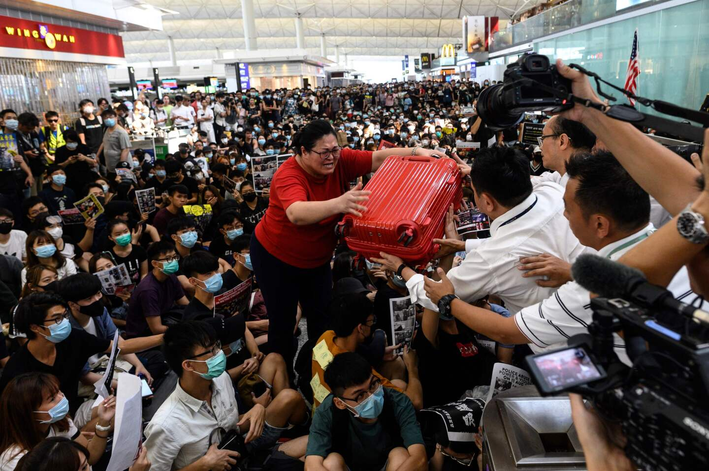 A tourist (C) gives her luggage to security guards as she tries to enter the departures gate during another demonstration by pro-democracy protesters at Hong Kong's international airport on August 13, 2019. - Protesters blocked passengers at departure halls of Hong Kong airport on August 13, a day after a sit-in forced authorities to cancel all flights to and from the major international hub. (Photo by Philip FONG / AFP)PHILIP FONG/AFP/Getty Images ** OUTS - ELSENT, FPG, CM - OUTS * NM, PH, VA if sourced by CT, LA or MoD **