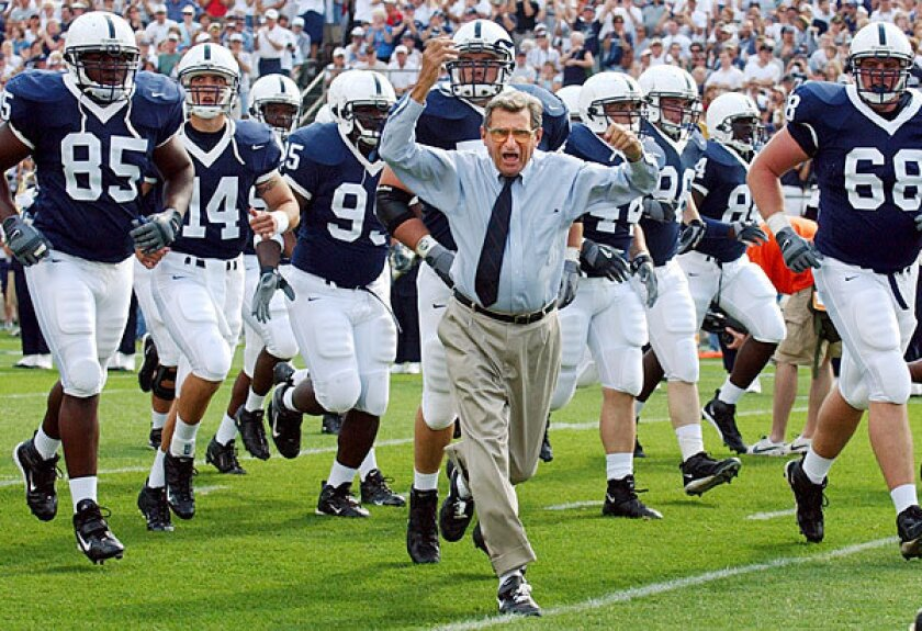 Coach Joe Paterno leads his Penn State team onto the field in 2004 for a game against Akron in State College, Pa.
