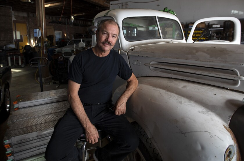 """Greg """"Reverend Gadget"""" Abbott, car inventor and EV whiz, in his shop in Los Angeles. He converts retro sports cars to electric power. He is sitting next to a 1947 Ford truck and Tesla car batteries."""