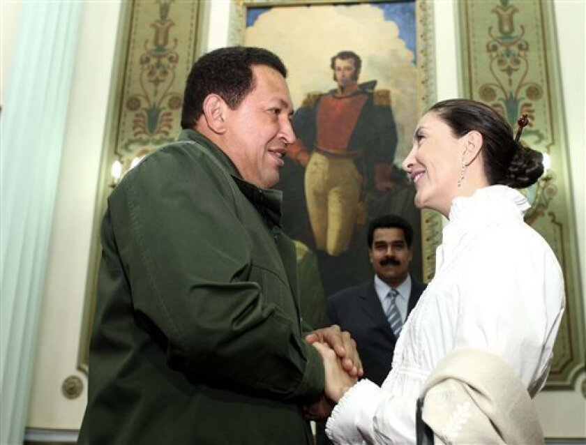 In this photo released by Miraflores Press Office, Venezuela's President Hugo Chavez greets former Colombian hostage Ingrid Betancourt, right, during a meeting at the Miraflores Presidential Palace in Caracas, Monday, Dec. 8, 2008. Betancourt was freed in July after being held more than six years in jungle camps by leftist rebels from the Revolutionary Armed Forces of Colombia, FARC. (AP Photo/Miraflores Press Office)