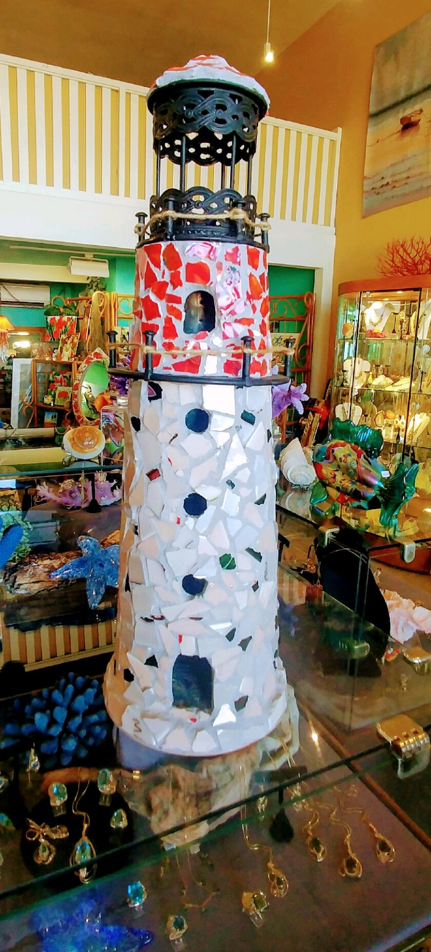 A mosaic lighthouse approximately 2 ½ to 3 feet high.