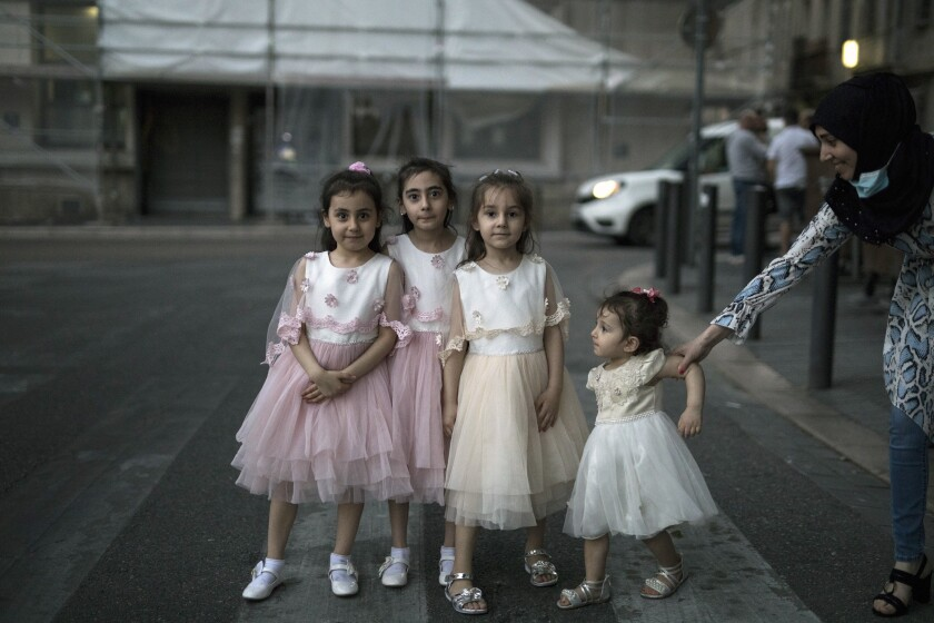 FILE - In this May 26, 2020, file photo, a mother poses her children wearing matching dresses in the street during an evening walk in Marseille, southern France, as France gradually lifts its COVID-19 lockdown. Just as summer beckons, Europeans are re-inhabiting their cafes, parks and beaches abandoned during months of lockdown to check the spread of the coronavirus. (AP Photo/Daniel Cole, File)