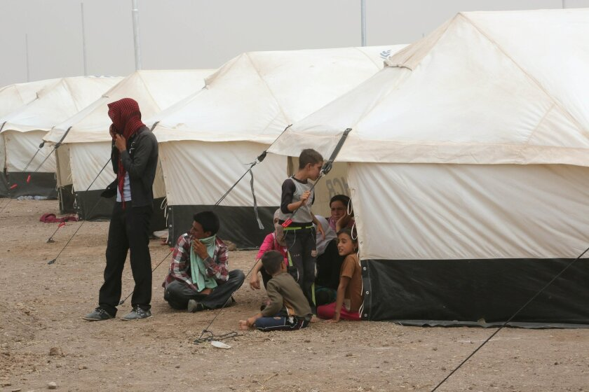 Displaced Iraqis settle at a new camp outside the Bajid Kandala camp in Feeshkhabour town, Iraq, Tuesday, Aug. 19, 2014. Some 1.5 million people have been displaced by fighting in Iraq since the Islamic State's rapid advance began in June, and thousands more have died. The scale of the humanitarian