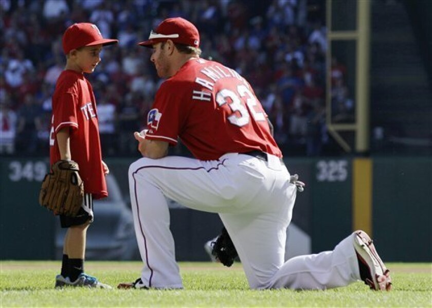 After throwing out a ceremonial first pitch, Cooper Stone, 6, talks with Texas Rangers left fielder Josh Hamilton (32) before Game 1 of baseball's American League division series playoffs against the Tampa Bay Rays Friday, Sept. 30, 2011, in Arlington, Texas. Hamilton threw the ball Shannon Stone was reaching for when he fell to his death behind the outfield wall in July. (AP Photo/Tony Gutierrez)