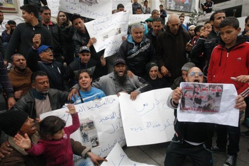 Street vendors demonstrate against the government after the death of a cigarette vendor who torched himself in a street died in Tunis, Wednesday, March 13, 2013. Adel Khadri who set himself alight on Tuesday in a street of the capital Tunis died from the severe burns he suffered, a medical official said Wednesday. (AP Photo/Amine Landoulsi)