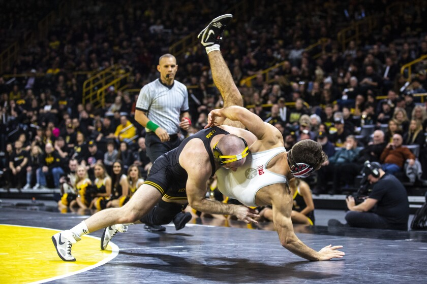 FILE - Iowa's Alex Marinelli, left, wrestles Ohio State's Ethan Smith at 165 pounds during a NCAA Big Ten Conference wrestling dual in Iowa City, Iowa, in this Friday, Jan. 24, 2020, file photo. The interruption to the season led to the cancellations of two duals, meaning the top-ranked Hawkeyes will go into the Big Ten championships having not competed since Feb. 7. The meet is Saturday and Sunday in State College, Pennsylvania. The Hawks won last year's conference title and Marinelli, 125-pounder Spencer Lee and 149-pounder Pat Lugo took individual championships.(Iowa City Press-Citizen via AP, File)