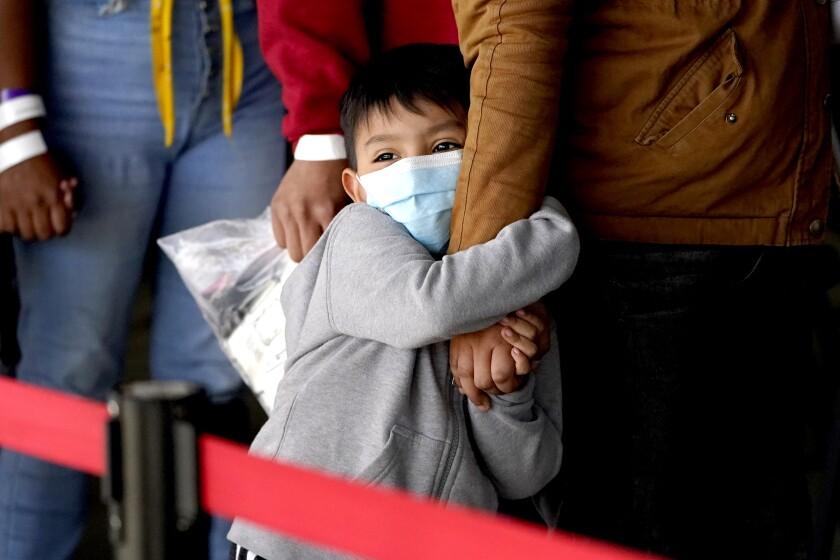 Un niño migrante abraza el brazo de una mujer mientras esperan a ser procesados