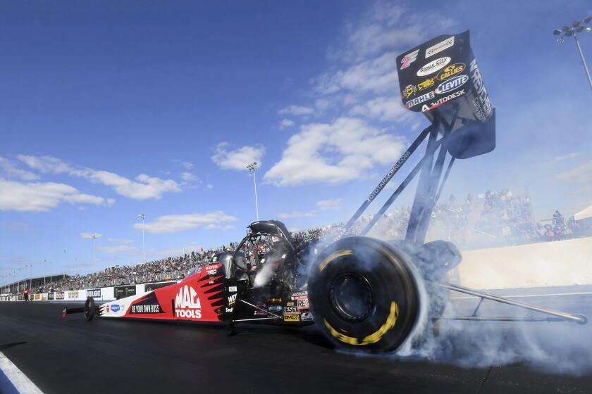 In this photo provided by the NHRA, Doug Kalitta does a burnout in Top Fuel at the Mopar Express Lane NHRA Midwest Nationals drag races at World Wide Technology Raceway on Sunday, Oct. 4, 2020, in Madison, Ill. Kalitta won for the fourth time at the St. Louis-area track, beating Steve Torrence in the final round with a 3.690-second run at 322.58 mph. (Marc Gewertz/NHRA via AP)