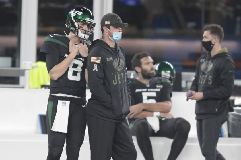 New York Jets quarterback Sam Darnold, center left, looks on from the sidelines during the first half of an NFL football game against the New England Patriots, Monday, Nov. 9, 2020, in East Rutherford, N.J. Jets quarterback Sam Darnold will be sidelined for a second straight game as he recovers from an injured right shoulder. Coach Adam Gase said Monday that Joe Flacco will start in Darnold's place when the winless Jets take on the Chargers in Los Angeles on Sunday.(AP Photo/Bill Kostroun)