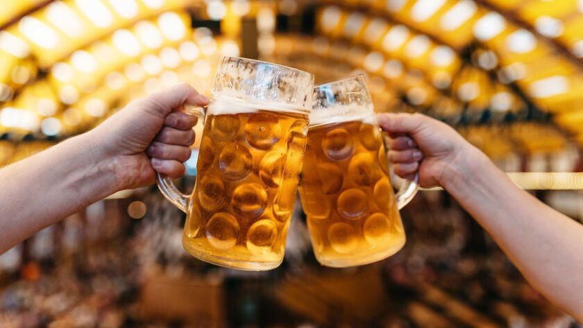 two hands clinking beer glasses in octoberfest marquee