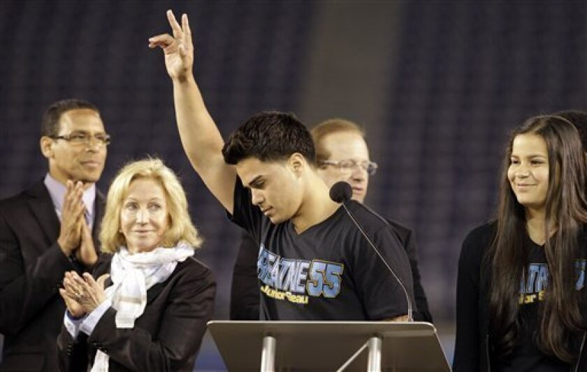 Tyler Seau, center, the son of Junior Seau, reacts to fans during a public memorial service for the late NFL football player Junior Seau at Qualcomm Stadium Friday, May 11, 2012, in San Diego. At rear are pastor Miles McPherson, left, San Diego Chargers owner Dean Spanos, second from right, his wif