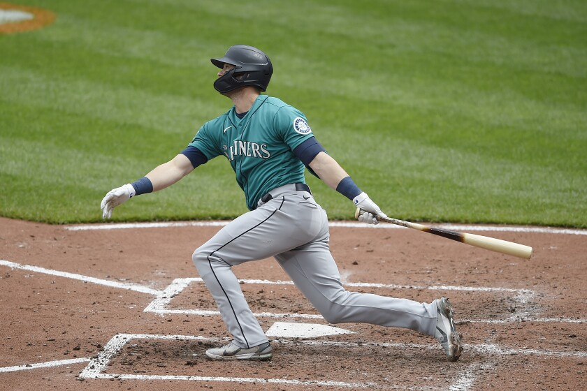 Seattle Mariners' Mitch Haniger follows through on a two run home run against the Baltimore Orioles in the fifth inning of the first game of a baseball doubleheader, Thursday, April 15, 2021, in Baltimore. (AP Photo/Gail Burton)