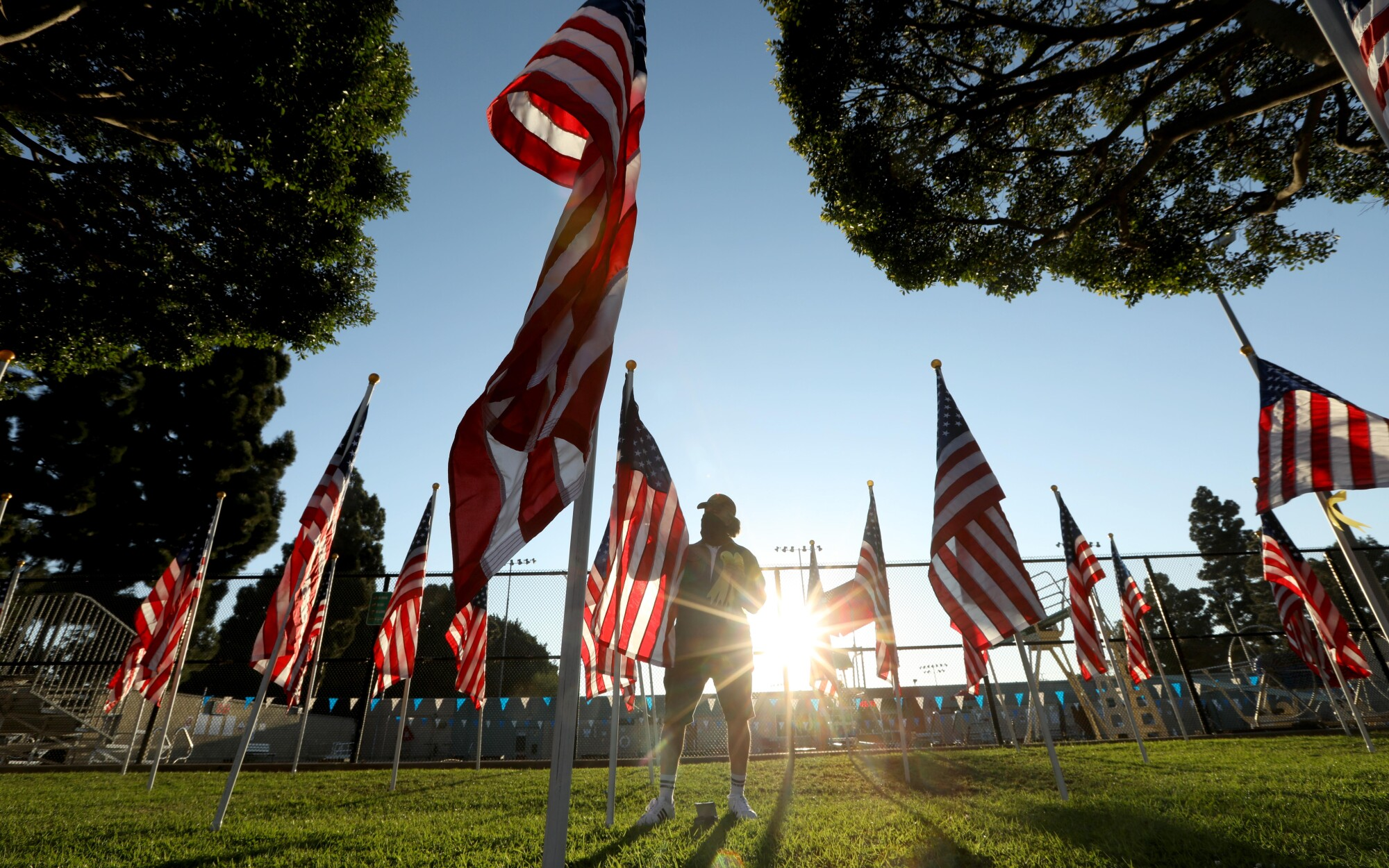 Jeff Cooper, president of Culver City Exchange, places a ribbon on each flag with the name of a veteran.