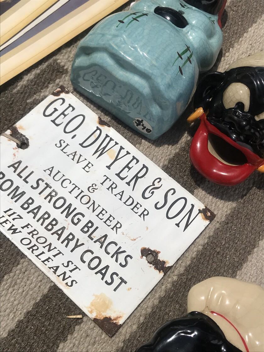 A sign of a slave auctioneer and a racist figurine caricature of a Black person sits on a table