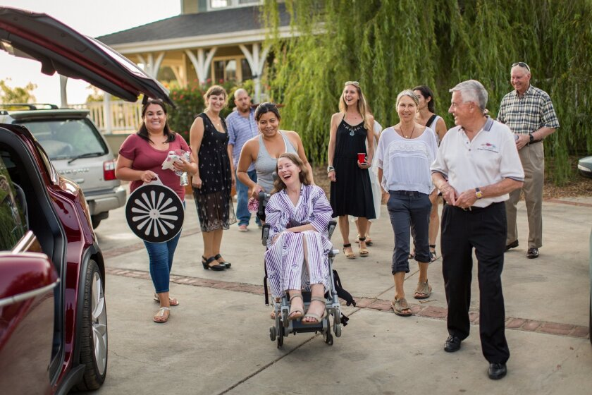 """This July 24, 2016 photo provided by Niels Alpert, Betsy Davis, center, is accompanied by friends and family for her first ride in a friends new Tesla to a hillside to end her life during a """"Right To Die Party"""" in Ojai, Calif. In early July, Davis emailed her closest friends and family to invite them to a two-day celebration, telling them: """"These circumstances are unlike any party you have attended before, requiring emotional stamina, centeredness, and openness. And one rule: No crying. """" The 41-year-old woman diagnosed with ALS, held the party to say goodbye before becoming one of the first California residents to take life-ending drugs under a new law that gave such an option to the terminally ill. (Niels Alpert via AP)"""