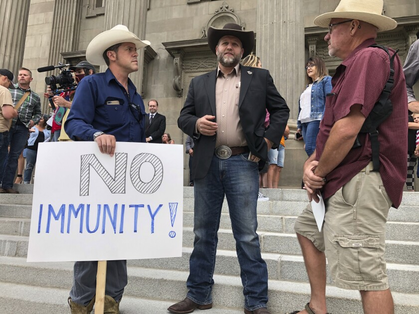 People in cowboy hats stand on steps of Idaho Capitol, one with a sign that says No Immunity