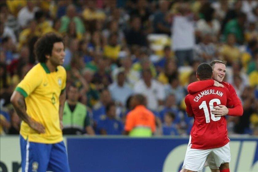 El jugador inglés Wayne Rooney (i) es marcado por el brasileño Thiago Silva (d), durante un partido amistoso entre Brasil e Inglaterra, en la reinauguración del estadio Maracaná en Río de Janeiro (Brasil). EFE