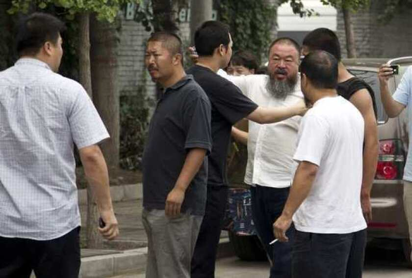 Ai Weiwei, third from right in the white, button-down shirt, argues with a policeman, center, outside his home in Beijing on Wednesday.