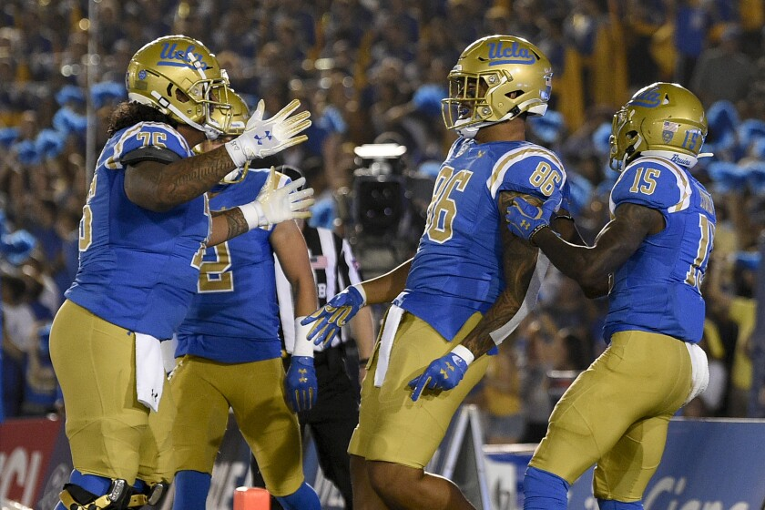UCLA tight end Devin Asiasi, second from right, celebrates his 16-yard touchdown catch in the first quarter.