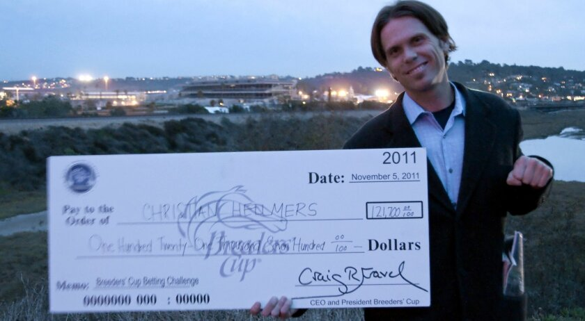 Christian Hellmers stands with his check from the Breeders' Cup betting challenge in front of the Del Mar racetrack, where he learned the ropes of betting at an early age. Photo: Claire Harlin