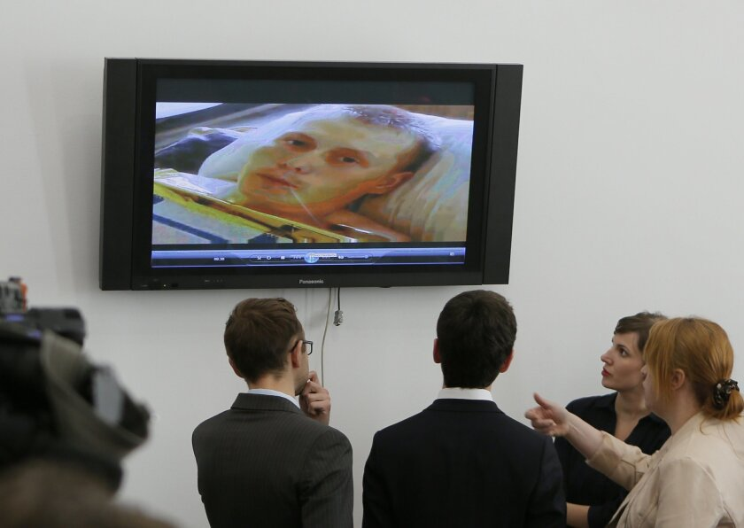Reporters look at the TV screen showing Alexander Alexandrov, a Russian Army soldier who was captured by Ukrainian military near the front line town of Shchastia in the Luhansk region, before a press conference in General Staff of Ukraine in Kiev, Ukraine, Monday, May 18, 2015. Two wounded Russian soldiers captured while fighting in war-torn eastern Ukraine have been transferred to a hospital in Kiev, Ukrainian officials said Monday as Moscow once again firmly denied any involvement in the fighting. The Russians were wounded and taken prisoner Saturday near the front line town of Shchastia in the separatist Luhansk region, Ukrainian officials reported. (AP Photo/Sergei Chuzavkov)