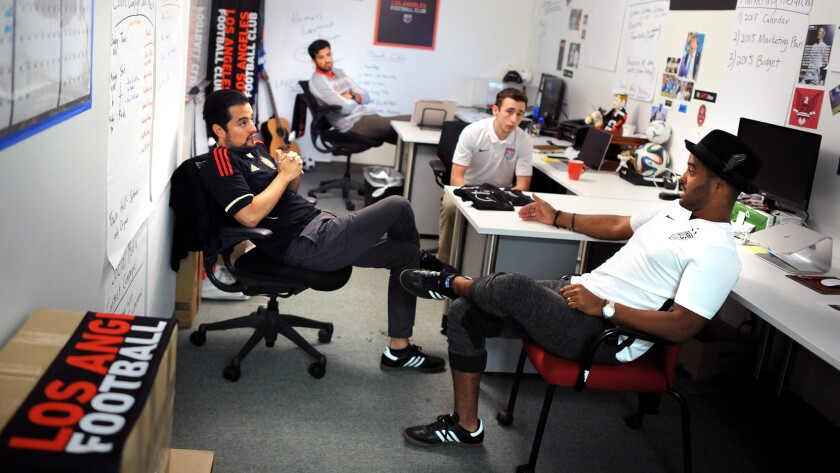 """LAFC marketing director Rich Orosco, left, talks with his co-workers in the """"war room"""" where planning takes place for the new professional soccer team that is coming to Los Angeles."""
