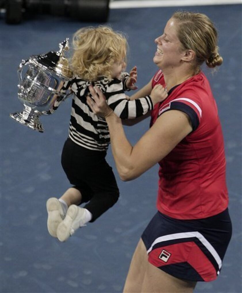 Kim Clijsters of Belgium lifts her daughter Jada after winning the women's championship over Caroline Wozniacki, of Denmark, at the U.S. Open tennis tournament in New York, Sunday, Sept. 13, 2009. (AP Photo/Kathy Willens)