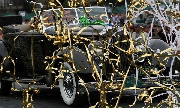 Joseph C. Cassini drives his 1934 Packard 1108 Twelve Dietrich Convertible Victoria onto the winners platform after being awarded the Best of Show award at the Pebble Beach Concours d'Elegance.